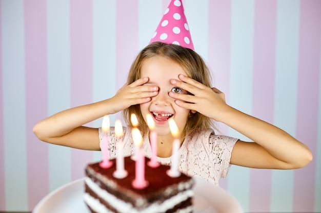 Mała blondynka w różowej czapce urodzinowej uśmiecha się, zamyka oczy, składa życzenie, zaskakuje czekoladowy tort ze świeczkami. dziecko obchodzi swoje urodziny.