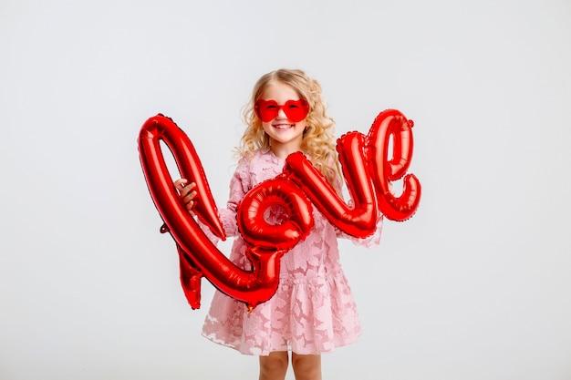 """Mała blondynka w różowej sukience trzyma w dłoniach napis """"miłość"""" z balonów na białej ścianie"""