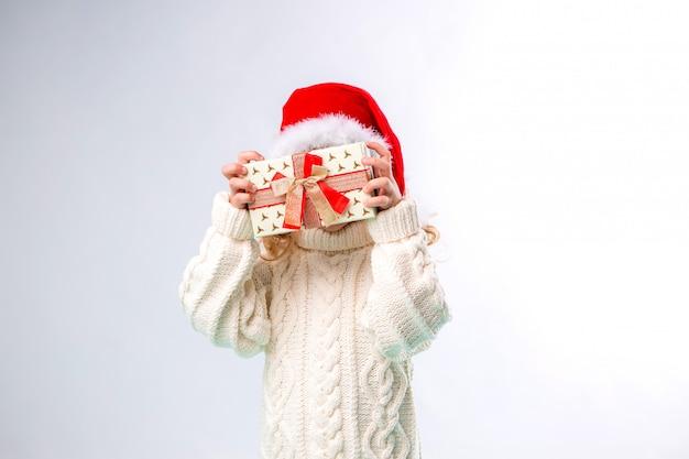 Mała blondynka w santa hat gospodarstwa pudełko