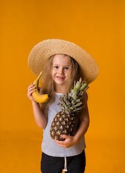 Mała blondynka w słomkowym kapeluszu trzyma banana i ananasa na żółtej powierzchni z miejscem na tekst