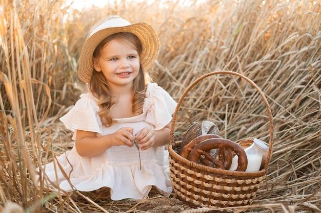 Mała blondynka w słomkowym kapeluszu z koszem chleba w polu pszenicy. ekologiczne produkty rolne.