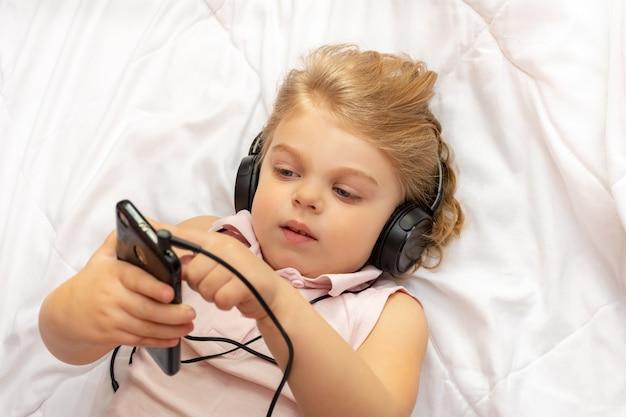 Mała blondynka w słuchawkach słucha muzyki