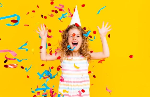 Mała blondynka w świątecznej czapce iw białej sukni łapie konfetti szczęśliwy uśmiech na żółtym tle.