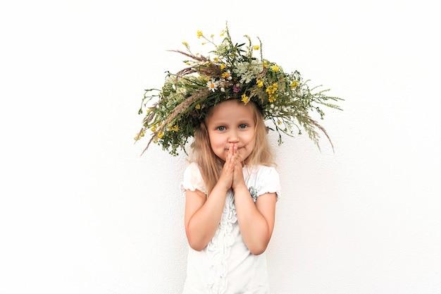 Mała blondynka w wieńcu z polnych kwiatów na tle białej ściany
