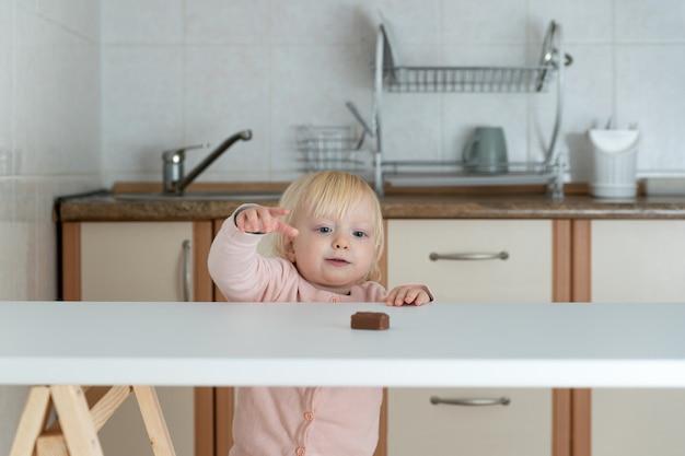 Mała blondynka wyciąga rękę po czekoladowe cukierki na stole. zakazane słodycze.
