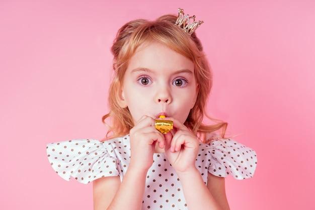 Mała blondynka z lokami fryzura w białej sukience w groszku 4-5 lat w studio na różowym tle dmuchanie, hałaśliwy róg-gwizdek przyjęcie urodzinowe świętuje ze złotą koroną głowy królowej