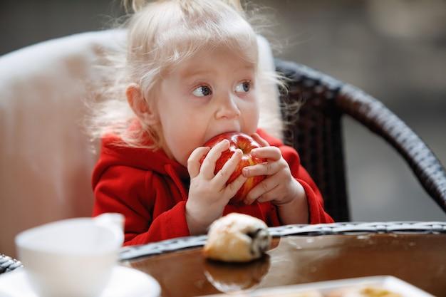 Mała blondynka z ogonem zjada jabłko przy stoliku w kawiarni.