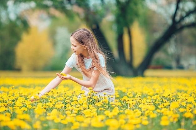 Mała blondynka zbiera kwiaty na łące pełnej żółtych dmuchawców