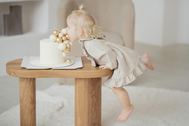 Mała blondynka zjada słodki tort z balonami na urodziny. ubrana w jasnobeżową stylową sukienkę i chodzi boso, świętuje święta