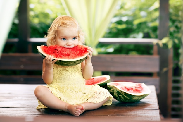 Mała blondynki dziewczyna je soczystego arbuza w ogródzie. dzieci jedzą owoce na ulicy. zdrowa żywność dla dzieci. ogrodnictwo dla małych dzieci.