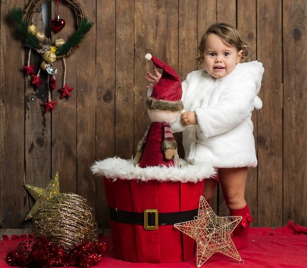 Mała blondynki dziewczyna jest ubranym białego żakiet na drewnie