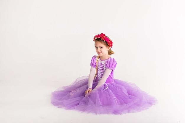 Mała blondynki dziewczyna jest ubranym purpurową czarodziejską princess suknię na białym tle. kostium dziecięcy na imprezę noworoczną