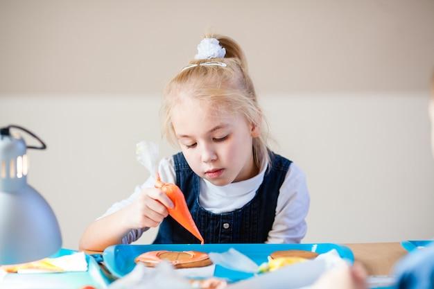 Mała blondynki dziewczyna przy warsztatem na piernikowym dekorowaniu z pomarańczowym cukrowym lodowaceniem
