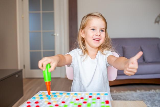 Mała blondynki dziewczyna siedzi przy stołem w domu bawić się z zabawkarskim śrubokrętem i multicolor śrubami. wczesna edukacja.