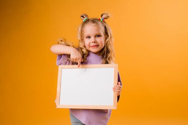 Mała blondynki dziewczyna uśmiecha się pustą deskę kreślarską i trzyma, przestrzeń dla teksta