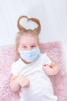 Mała blondynki dziewczyna w ochronnej medycznej masce na jej twarzy lying on the beach na ono uśmiecha się i podłoga. włosy w kształcie serca, pozytywne emocje