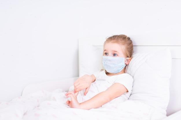 Mała blondynki dziewczyna w ochronnej medycznej maski lying on the beach w białym łóżku w białym pokoju.