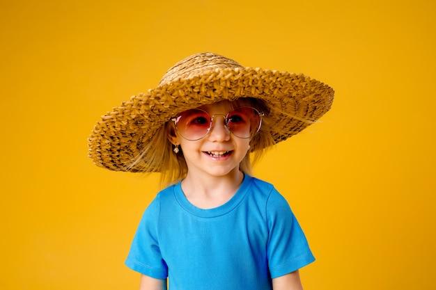 Mała blondynki dziewczyna w okularach przeciwsłonecznych i słomianym kapeluszu w błękitów ubraniach na żółtym tle odizolowywa