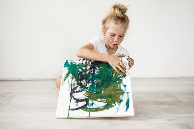 Mała blondynki żeńskie dziecko z hairbn i piegami jest ubranym białą koszulkę zajmującą z jej obrazem. urocza, urocza dziewczyna siedzi na podłodze z kolorowym płótnem na kolanach.