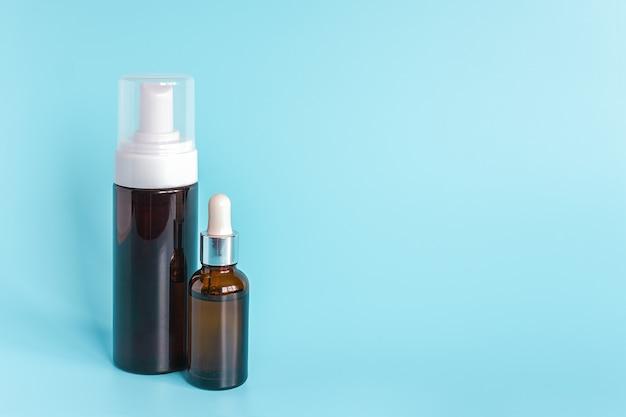 Mała brązowa butelka z kroplomierzem i duża butelka z białym dozownikiem. produkt kosmetyczny concept
