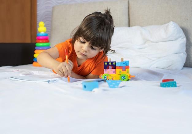 Mała brązowa włosiana dziewczyna z brązowymi oczami. 3 lata. malowanie piórem w notesie. siedzieć na kanapie w domu.