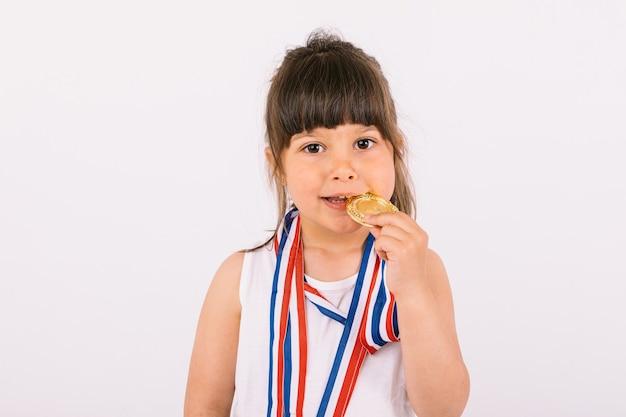 Mała brązowowłosa dziewczynka z medalami mistrza sportu, gryząc je. koncepcja sportu i zwycięstwa