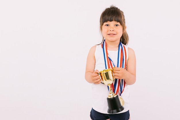 Mała brązowowłosa dziewczynka z medalami mistrza sportu, trzymająca obiema rękami trofeum. koncepcja sportu i zwycięstwa