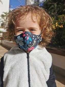 Mała brazylijska dziewczyna uśmiecha się za pomocą maski na zewnątrz.