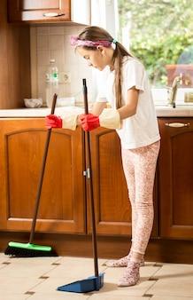 Mała brunetka dziewczynka czyści podłogę w kuchni z miotłą i szufelką