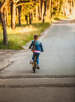 Mała brunetka dziewczynka jedzie na rowerze po drodze w lesie o zachodzie słońca