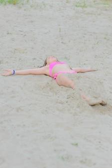 Mała brunetka dziewczynka w różowym bikini siedzi na piasku. zrelaksować się. dziewczynka latem 9 lat