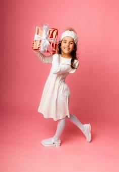 Mała brunetka z długimi włosami w czapce zimowej trzyma prezent na różowym tle.