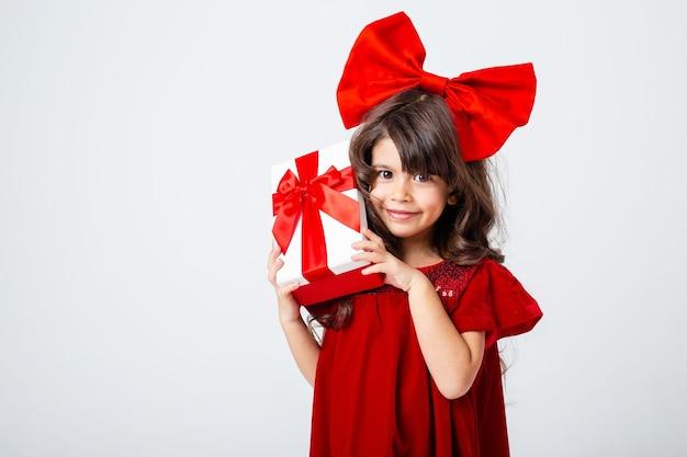 Mała brunetka z dużą kokardą na głowie trzyma w dłoniach pudełko na prezent