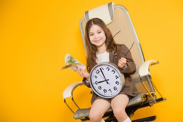 Mała brunetki dziewczyna z zegarami i gotówką w krześle