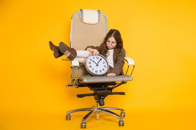 Mała brunetki dziewczyna z zegarami w krześle