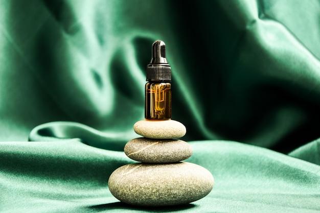 Mała butelka serum na stos kamieni bazaltowych na tle zielonej satynowej tkaniny. modny kolor. zakraplacz do pipet beauty na piramidzie kamyków. medycyna naturalna, krople do nosa, krople do oczu