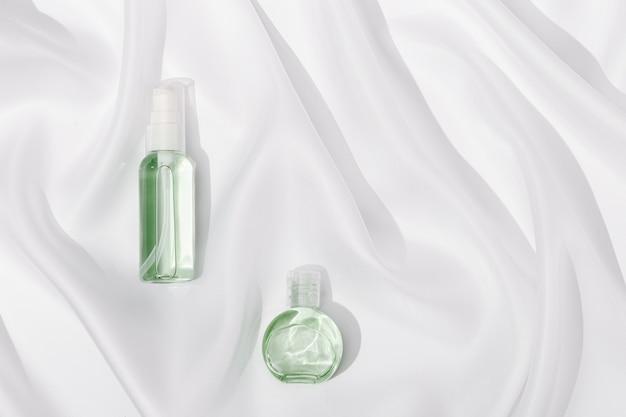 Mała butelka z przezroczystym żelem na białej satynowej fakturze