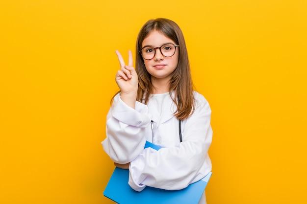 Mała caucasian dziewczyna jest ubranym doktorskiego kostium pokazuje numer dwa z palcami.