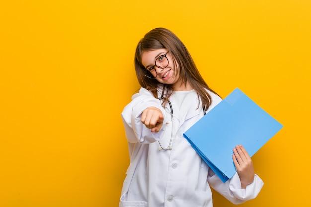 Mała caucasian dziewczyna jest ubranym doktorskiego kostiumu rozochoconych uśmiechy wskazuje przód