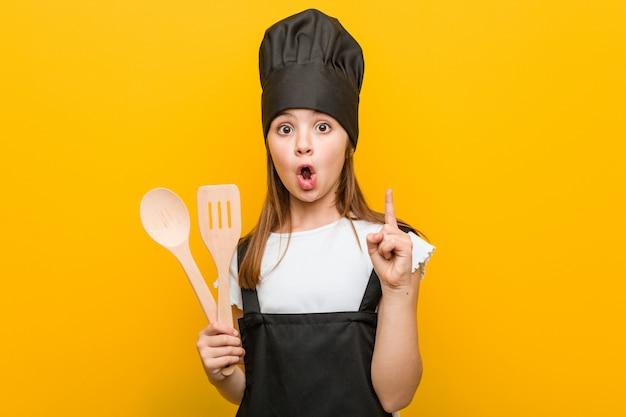 Mała caucasian dziewczyna jest ubranym szefa kuchni kostium ma niektóre doskonałego pomysł, pojęcie twórczość.