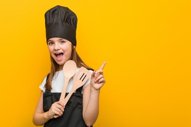 Mała caucasian dziewczyna jest ubranym szefa kuchni kostium ono uśmiecha się radośnie wskazujący z palcem wskazującym daleko od.