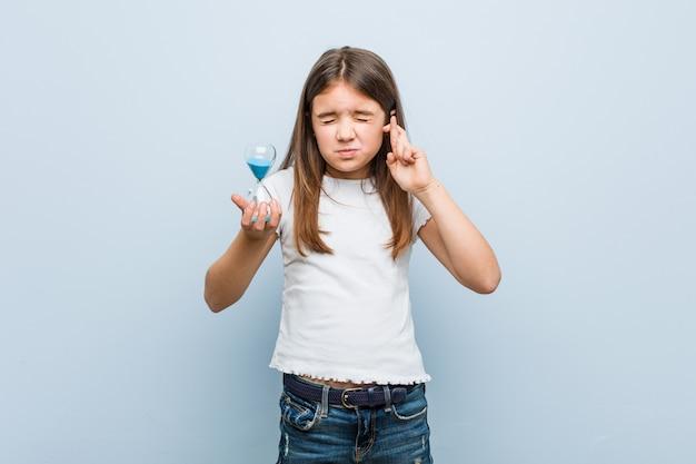 Mała caucasian dziewczyna trzyma klepsydrę krzyżuje palce dla mieć szczęście