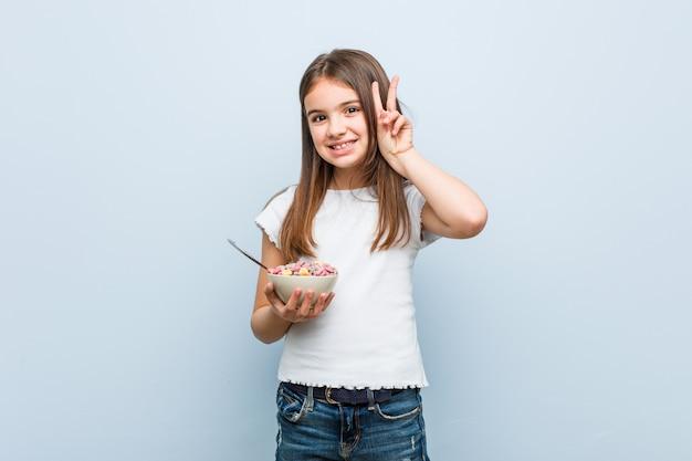 Mała caucasian dziewczyna trzyma zboże puchar pokazuje zwycięstwo znaka i ono uśmiecha się szeroko.