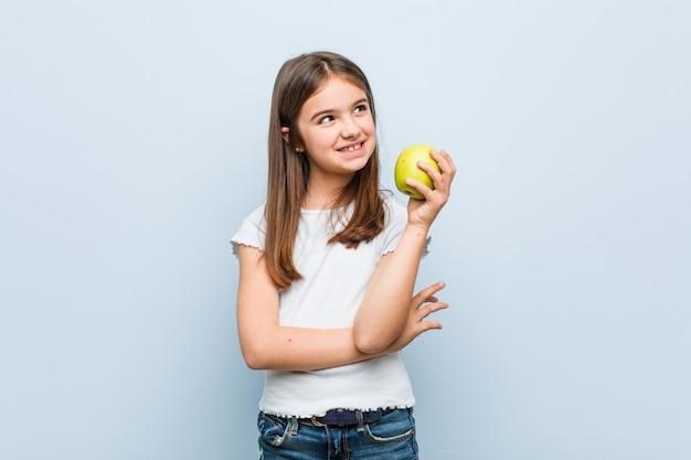 Mała caucasian dziewczyna trzyma zielonego jabłka ono uśmiecha się ufny z krzyżować rękami