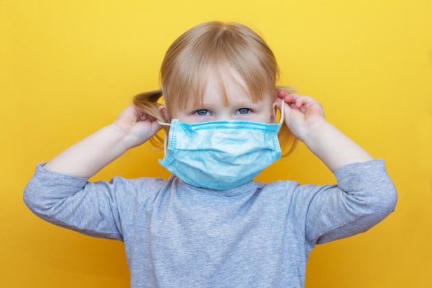 Mała caucasian dziewczyna ubiera ochronną maskę na żółtym backgraund