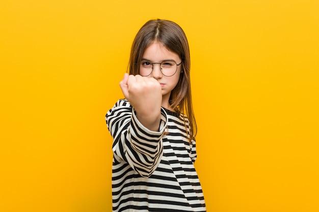 Mała caucasian śliczna dziewczyna pokazuje pięść, agresywny wyraz twarzy.