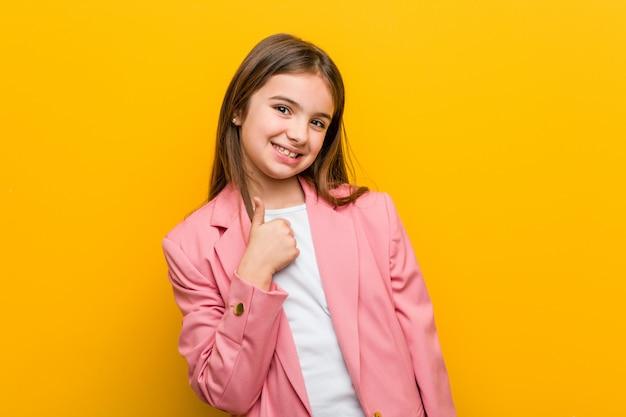 Mała caucasian śliczna dziewczyna uśmiecha się kciuk up i podnosi