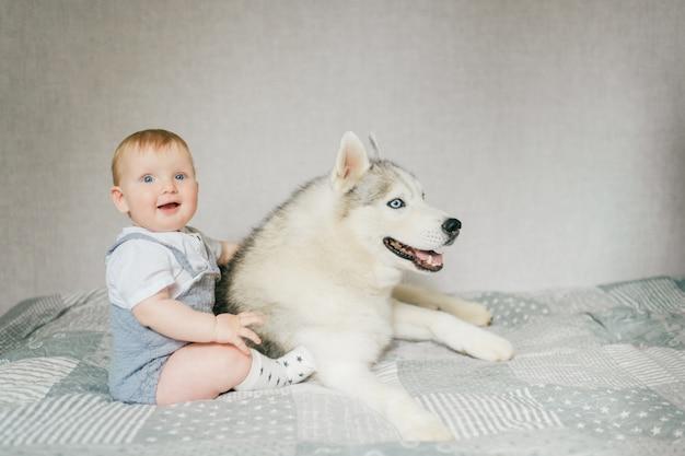 Mała chłopiec bawić się z szczeniakiem na łóżku