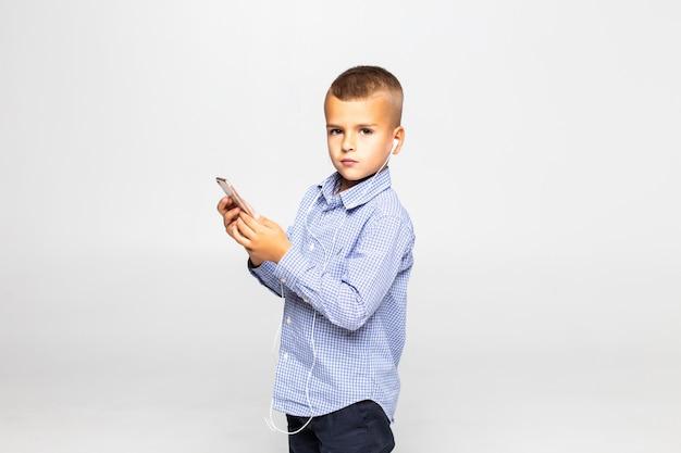 Mała chłopiec w hełmofonach słucha muzykę odizolowywającą na biel ścianie
