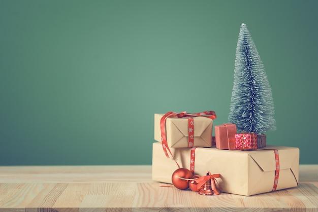 Mała choinka i pudełka z prezentami na drewnianym stole.